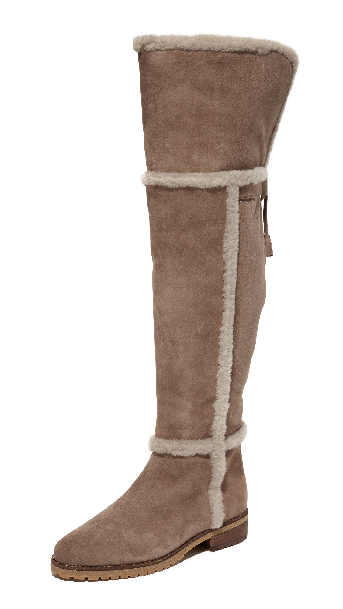 These over the knee Frye boots are crafted in velvety suede and are fully lined in shearling. Tie detail at split top line. Exposed inside zip. Lug sole. Fur: Dyed lamb shearling, from Spain. Leather: Sheepskin.