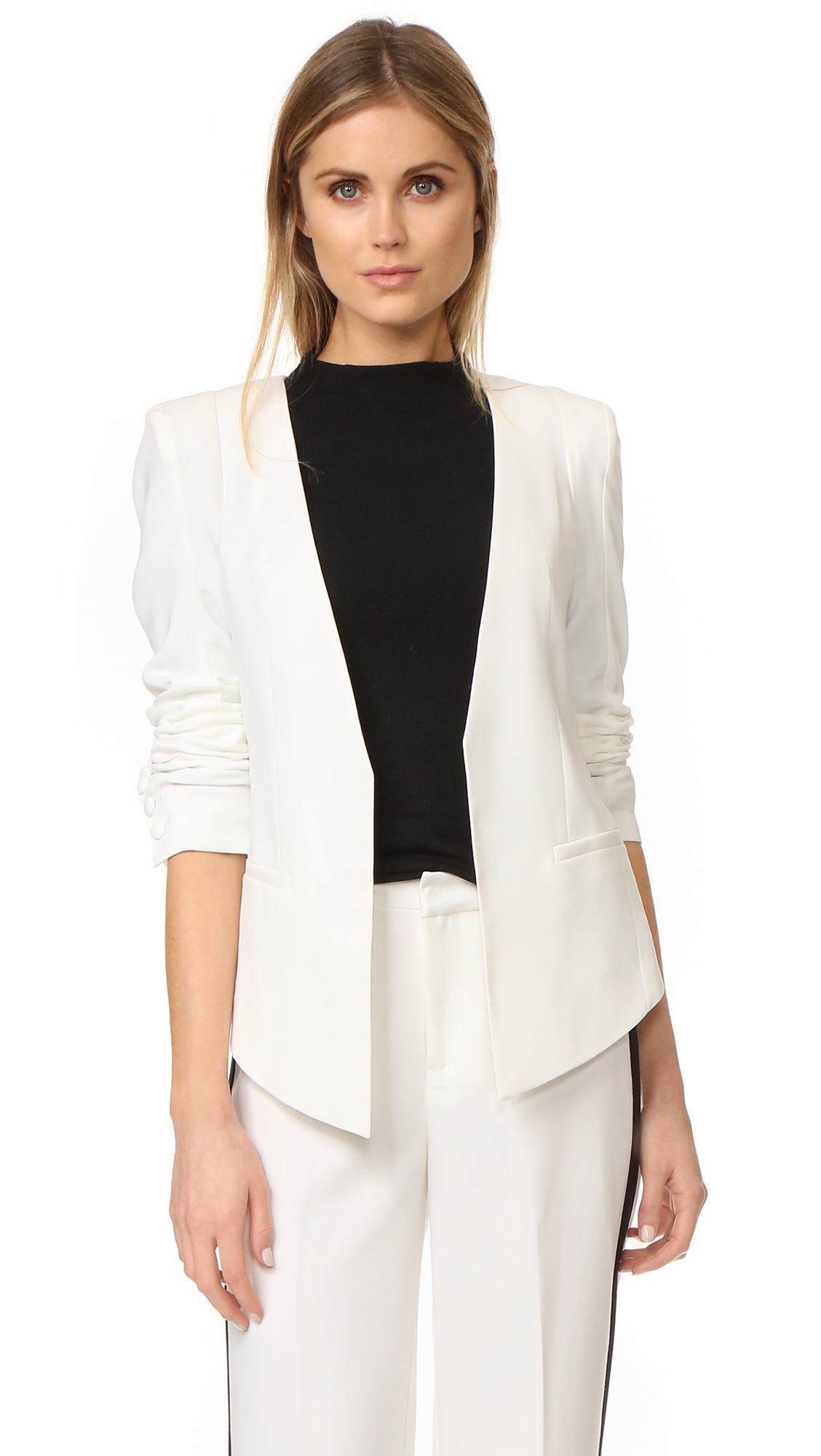 A unique blazer with a high low silhouette from James Jeans. Open placket. Welt front pockets. Padded shoulders. Button cuffs. Lined. Fabric: Suiting. 85% polyester/15% spandex. Dry clean. Made in the USA. Measurements Length 1: 27.5in / 70cm, from