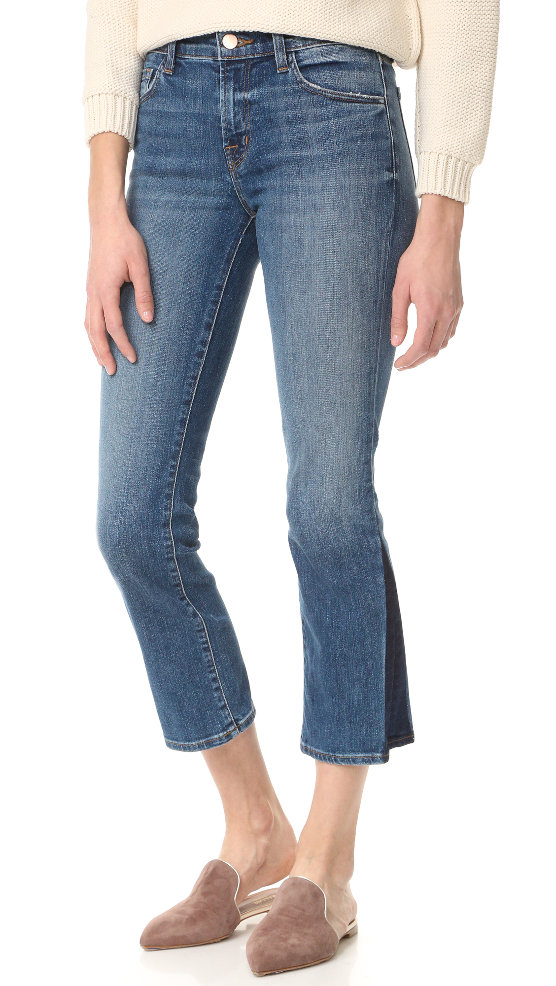 Inky overdye details the cuffs of these cropped J Brand boot cut jeans. 5 pocket styling. Button closure and zip fly. Fabric: Stretch denim. 98% cotton/2% polyurethane. Wash cold. Made in the USA. Imported materials. Measurements Rise: 9in / 23