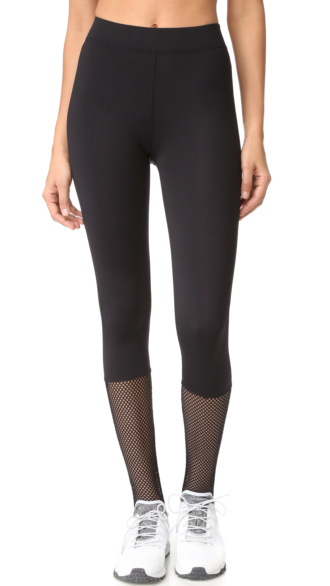 Mesh panels lend a graphic element to these sleek KORAL ACTIVEWEAR workout leggings. Covered elastic waist. Stirrup cuffs. Fabric: Performance jersey. Shell: 86% nylon/14% elastane. Trim: 89% polyester/11% spandex. Wash cold. Made in the USA. Imported materials. Measurements