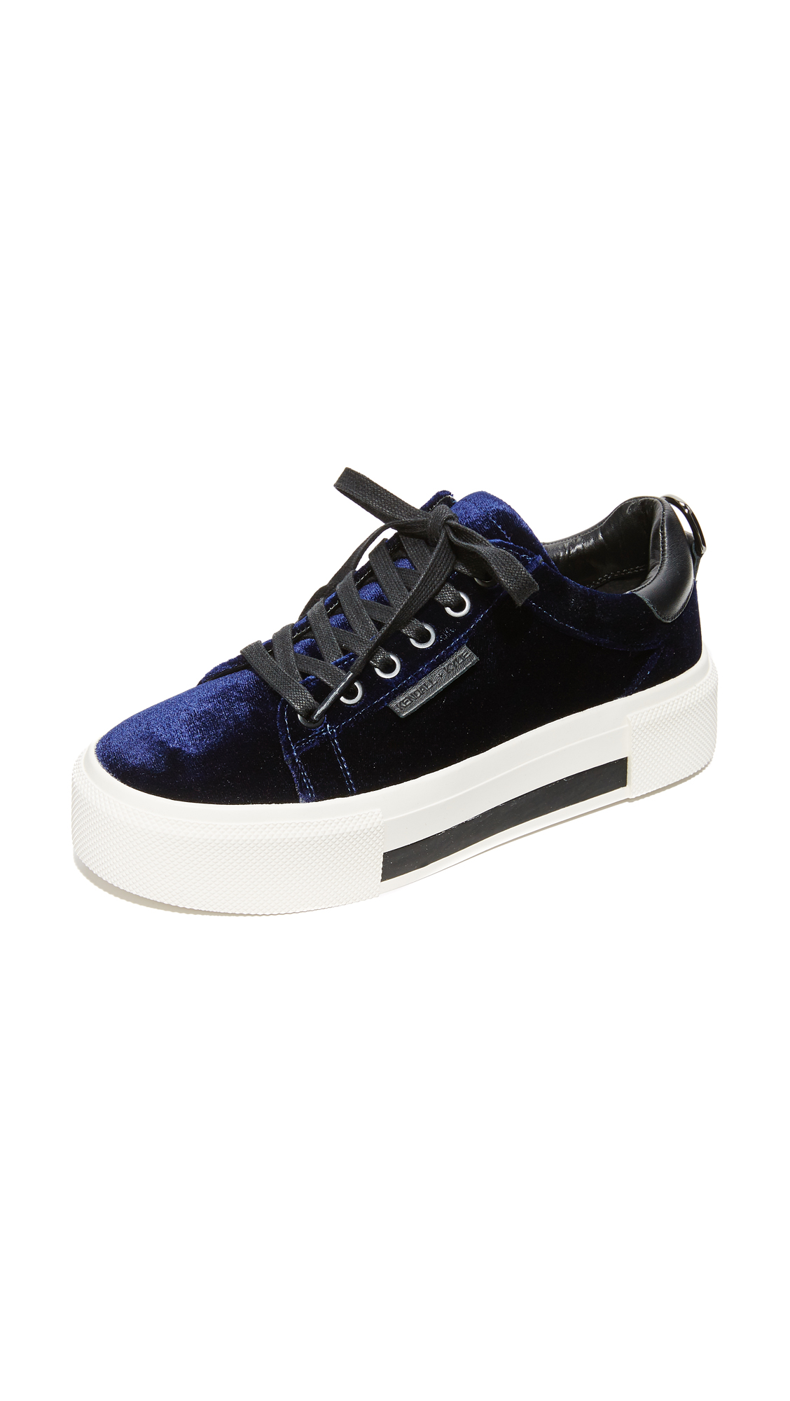 A striped platform adds a substantial lift to these stylish velvet KENDALL + KYLIE sneakers. Metal D ring accent at the leather heel cap. Padded collar and footbed. Lace up closure. Rubber sole. Fabric: Velvet. Imported, China.