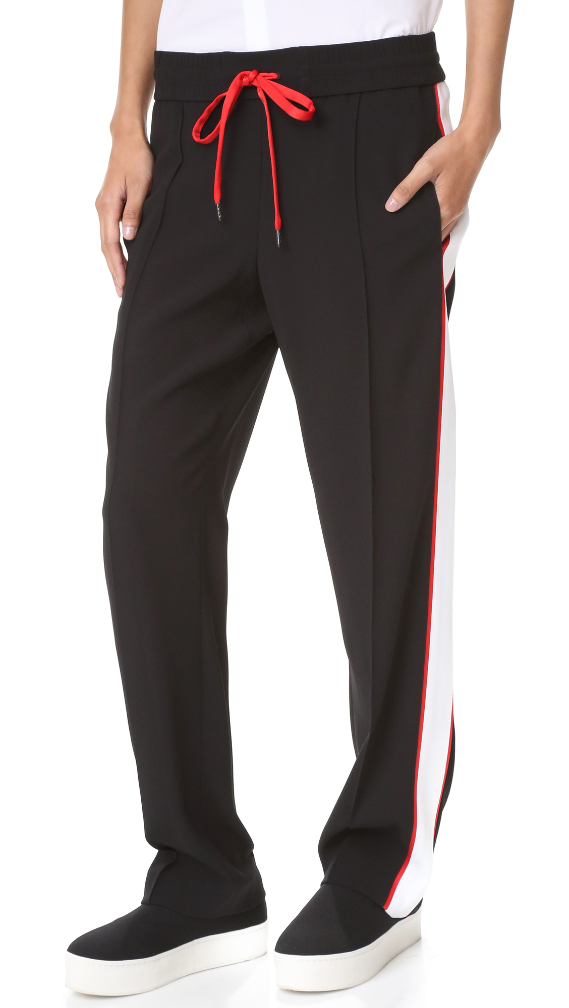 Bold stripes and a contrast drawstring give these wide leg KENZO pants an athletic inspired look. On seam pockets. Smocked waistband. Fabric: Crepe. 82% triacetate/18% polyester. Dry clean. Imported, Slovakia (Slovak Republic). Measurements Rise: 10.75in / 27cm Inseam: 30.25