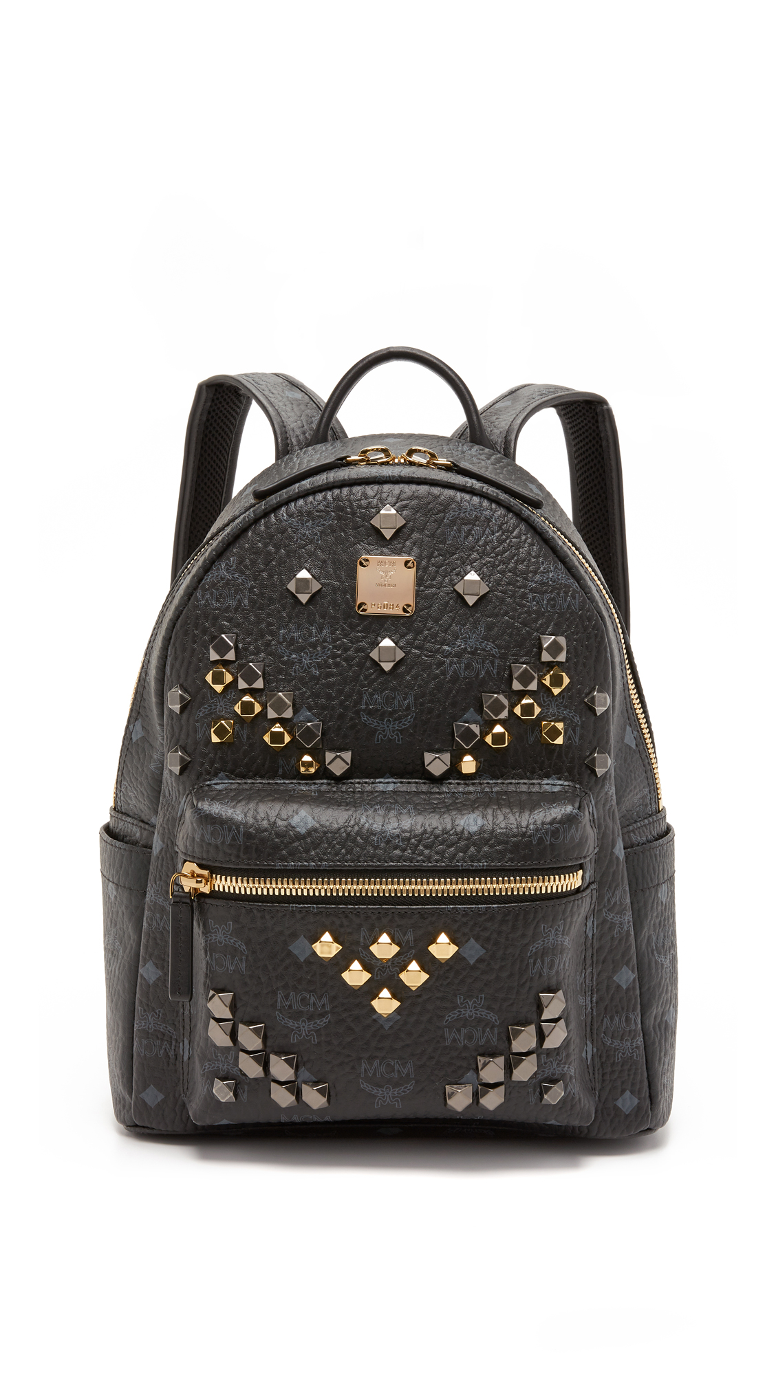 Multifaceted mixed metal studs dot the front of this monogrammed MCM backpack. Zip front pocket and slim side pockets. Wraparound top zip and unlined, 1 pocket interior. Locker loop and adjustable shoulder straps. Dust bag included. Fabric:
