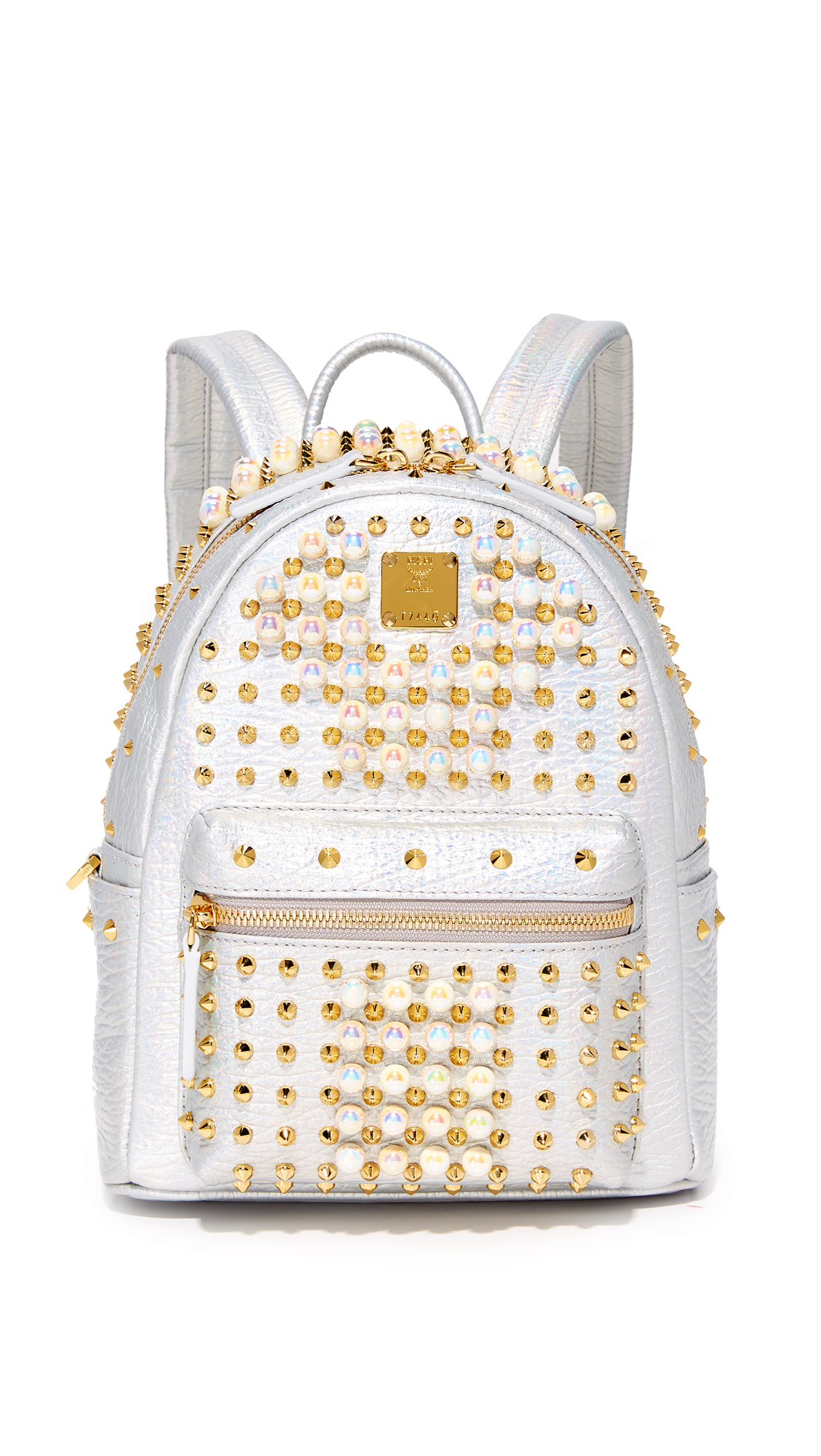 A metallic MCM backpack with eye catching faux pearls and studs. Zip front pocket and slim side pockets. Wraparound top zip and leather lined, 1 pocket interior. Locker loop and adjustable shoulder straps. Dust bag included. Leather: