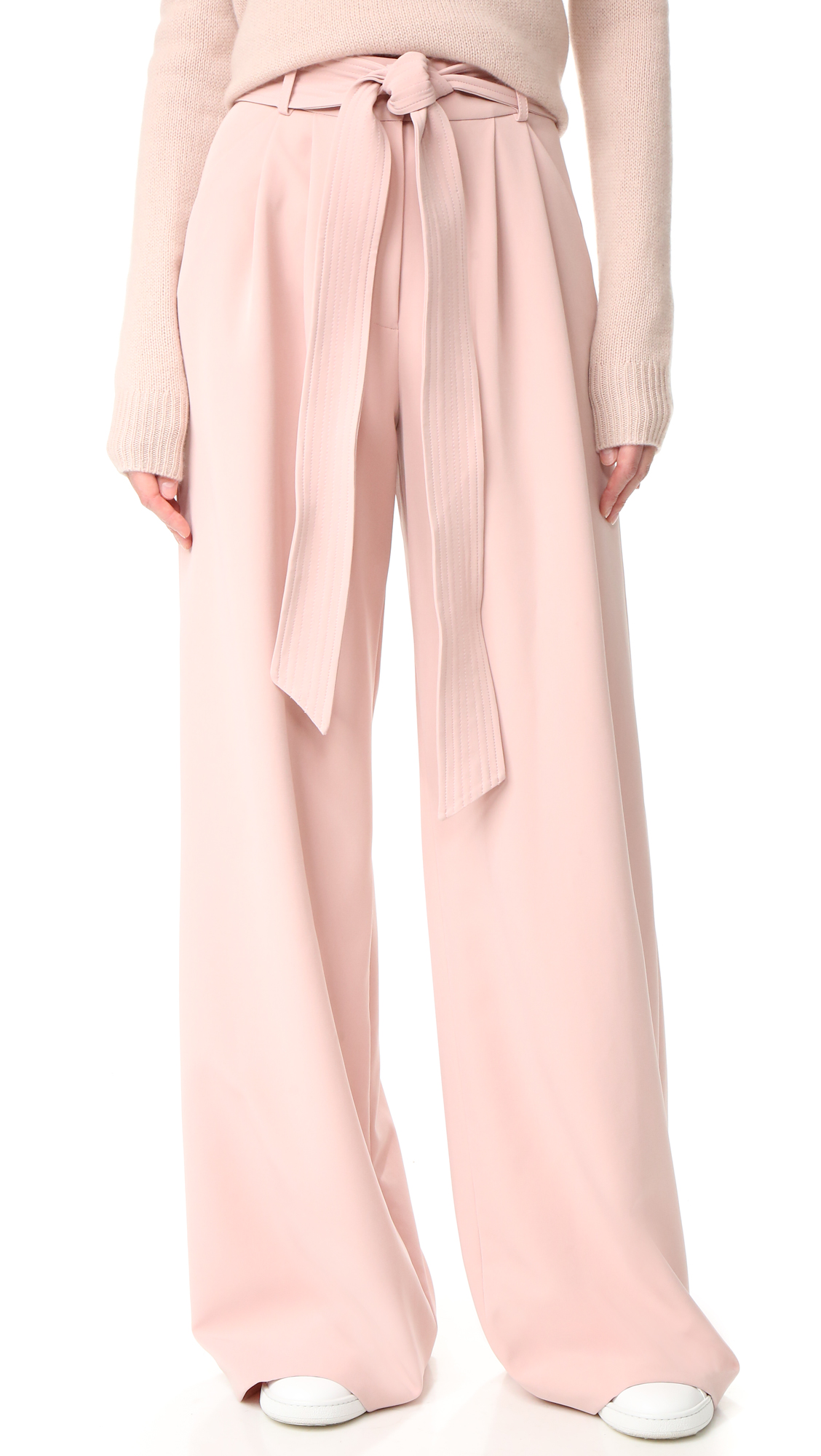 An optional, topstitched belt cinches the high waist on these wide leg Milly pants. Slant front pockets. Hook and eye closure and zip fly. Fabric: Stretch crepe. 90% polyester/10% elastane. Dry clean. Made in the USA. Fabric