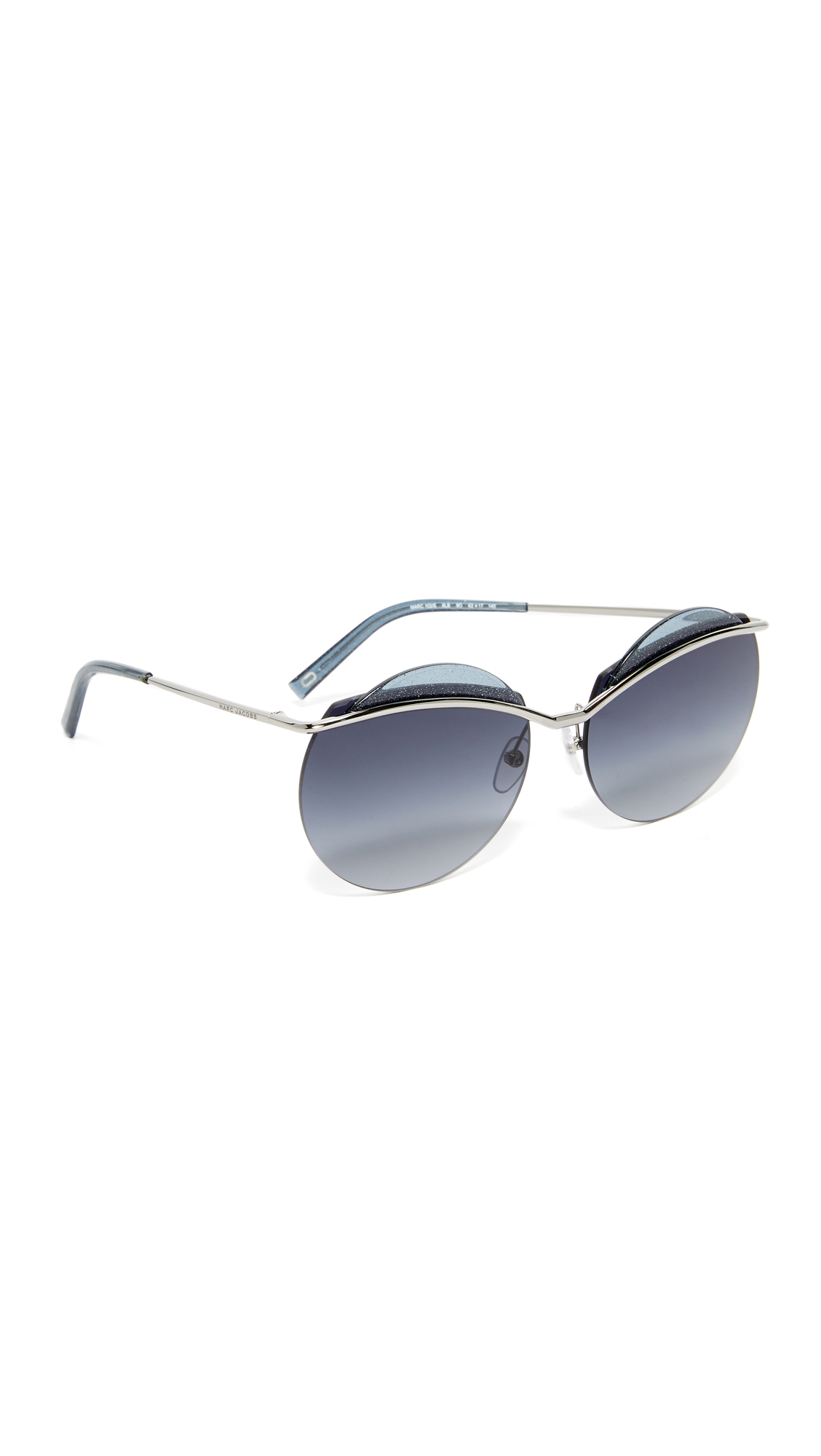 Futuristic Marc Jacobs sunglasses with a curving bridge and glittery trim. Acetate tips. Gradient lenses. Hardshell case and cleaning cloth included. Round frame. Non polarized lenses. Imported, China. Measurements Width: 6in / 15cm Height: 2.25in / 6cm Lens