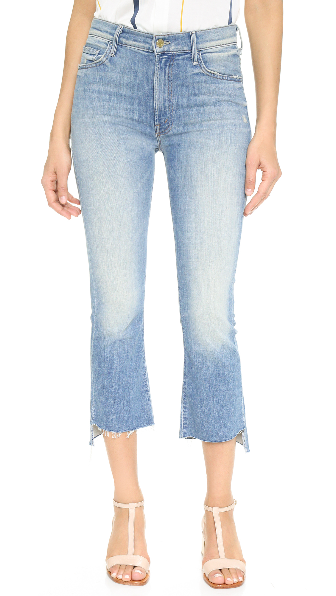 Flared MOTHER jeans with cropped, raw edge cuffs. A dirtied wash and heavy fading lends vintage appeal. 5 pocket styling. Single button closure and zip fly. Fabric: Stretch denim. 93% cotton/6% polyester/1% elastane. Wash cold. Made in the