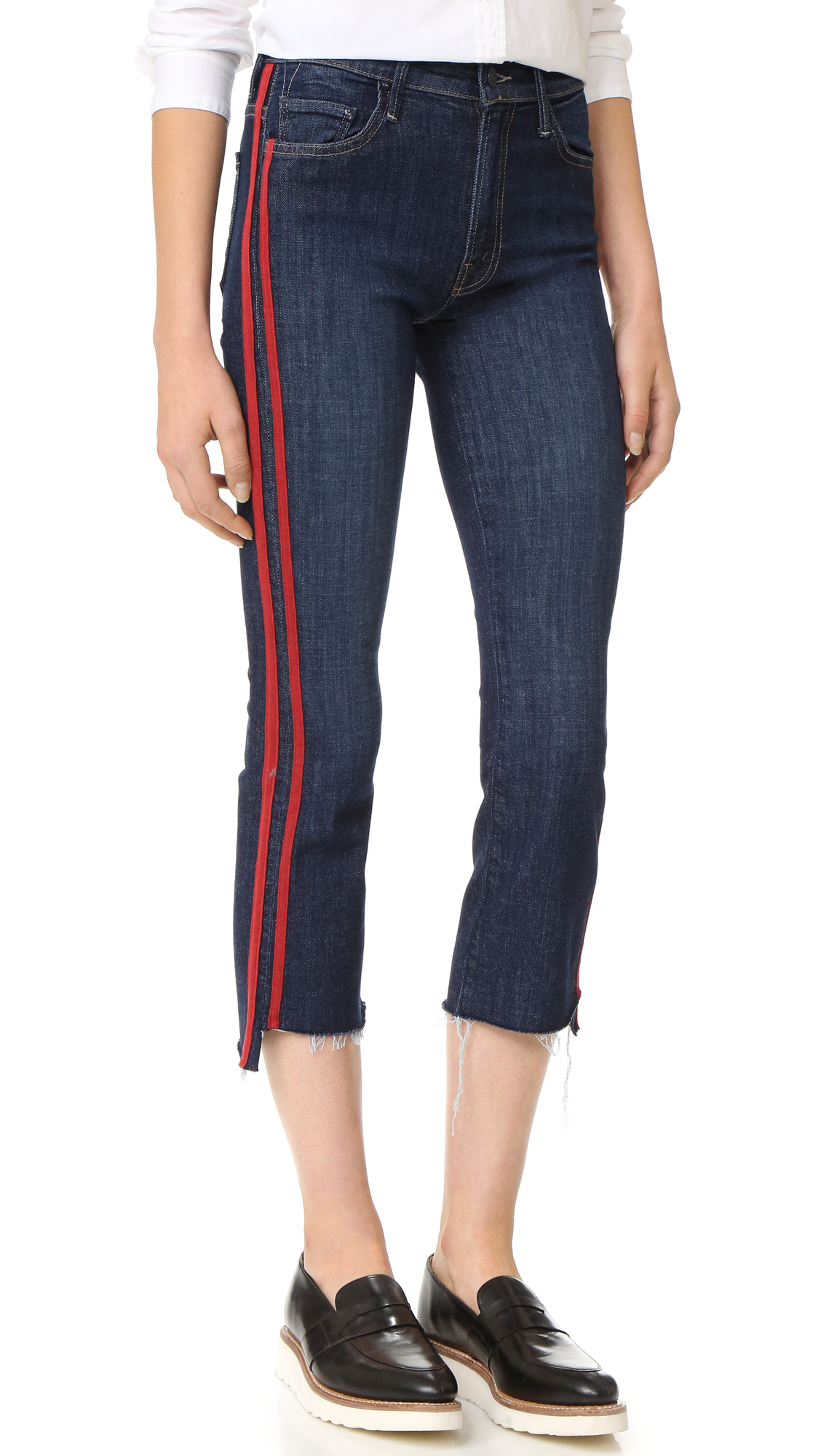 Contrast stripes accentuate the outseam on these high waisted MOTHER cropped jeans. Raw, notched hem. 5 pocket styling. Button closure and zip fly. Fabric: Stretch denim. 93% cotton/6% polyester/1% elastane. Wash cold. Made in the USA. Imported materials.
