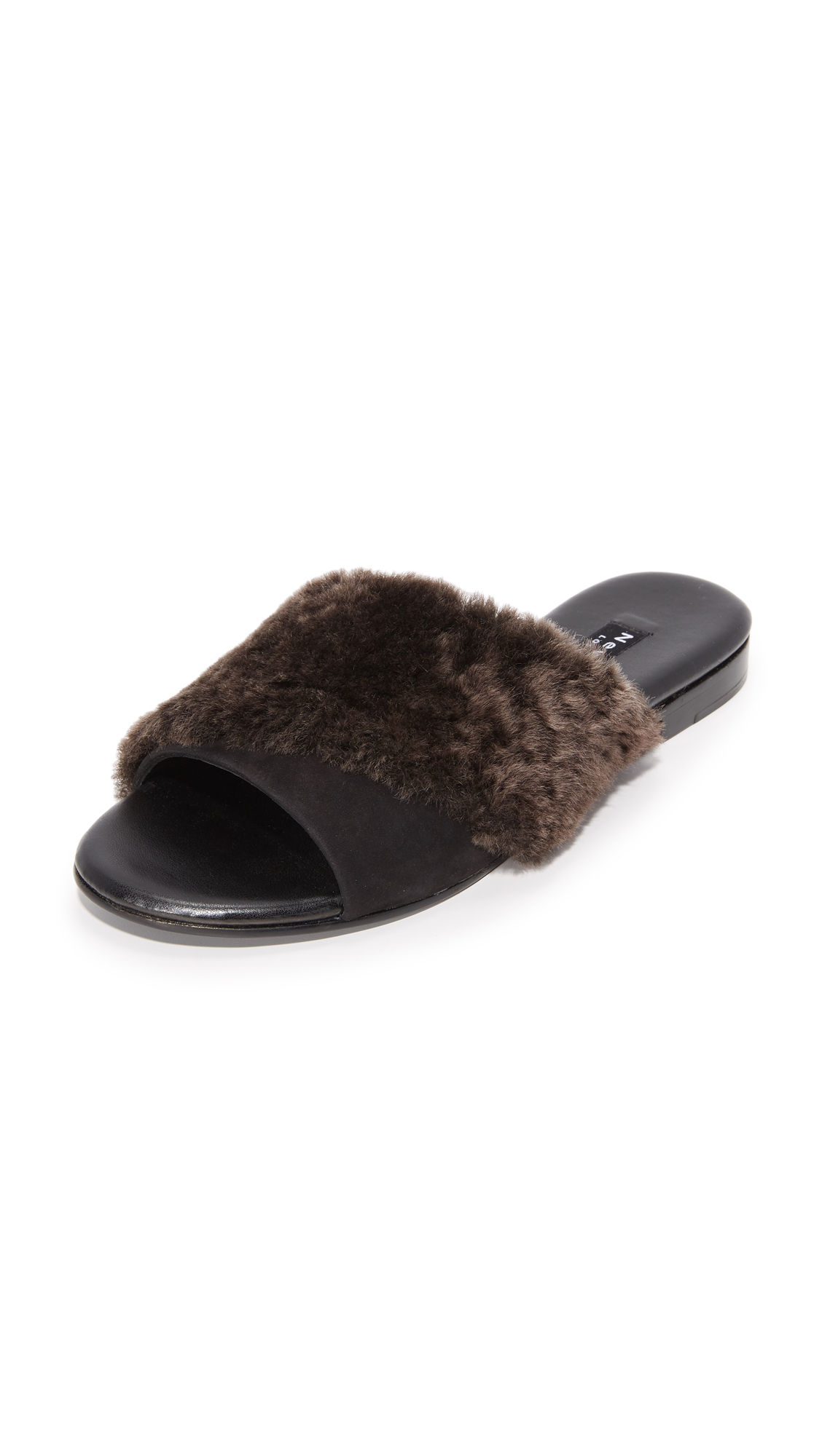A plush shearling strap crisscrosses the suede vamp on these casual Newbark slide sandals. Low, stacked heel and leather sole. Fur: Dyed lamb shearling, from the USA. Leather: Calfskin. Made in the USA. This item cannot