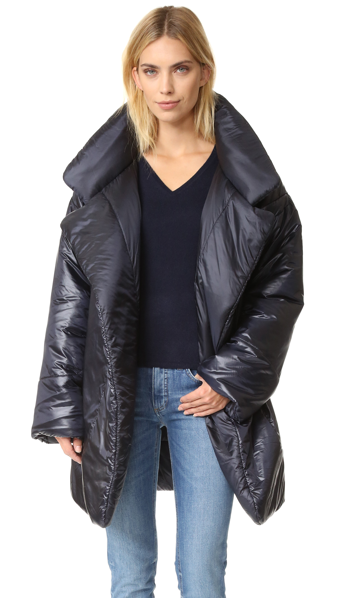 A warm, fiber filled Norma Kamali coat with lustrous sheen. The optional self belt cinches the loose, open silhouette. Long sleeves. Lined. Fabric: Glossy technical weave. Shell: 100% nylon. Fill: 100% polyester. Spot clean. Made in the USA.