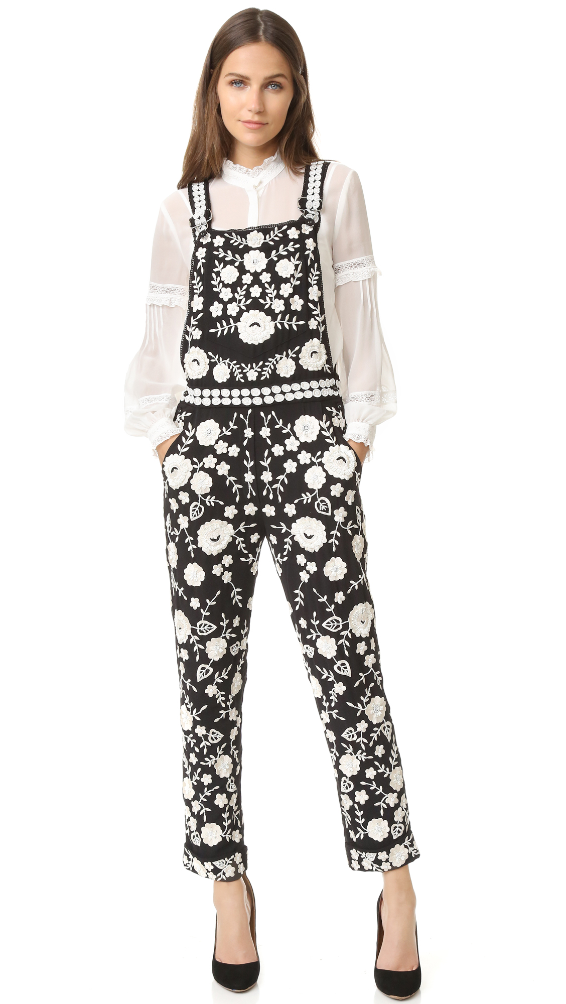 Statement making Needle & Thread overalls, covered with floral lace and detailed with intricate beading. Slant hip pockets, patch back pockets, and patch bib pocket. Adjustable shoulder straps. Fabric: Crepe. Shell: 100% polyester. Trim: 93% cotton/7% spandex. Dry clean.