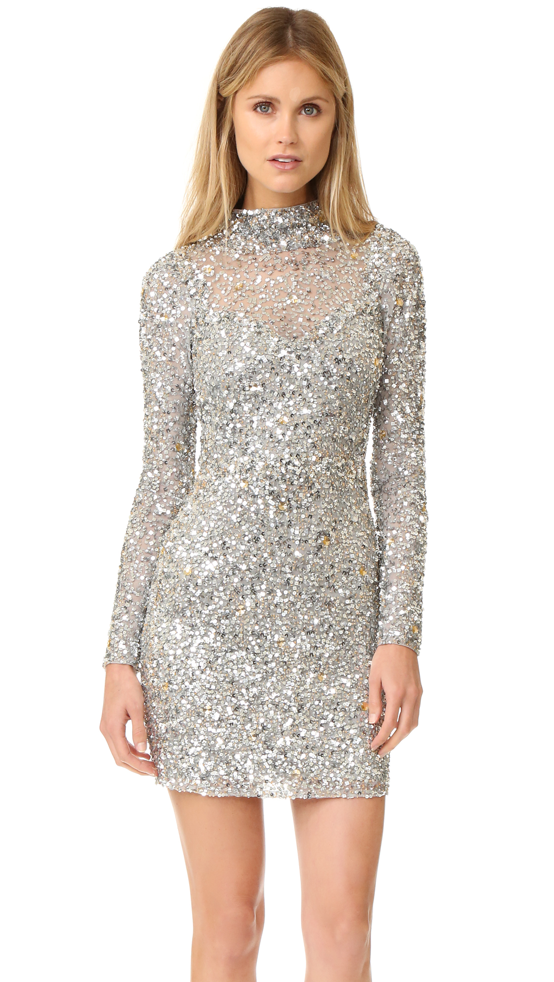 A formfitting Parker mini dress with eye catching crystals and sequins. Open back. Long sleeves. Button closure at neckline and hidden back zip. Lined. Fabric: Sequined mesh. Shell: 100% nylon. Lining: 100% polyester. Professional spot clean. Imported, India.
