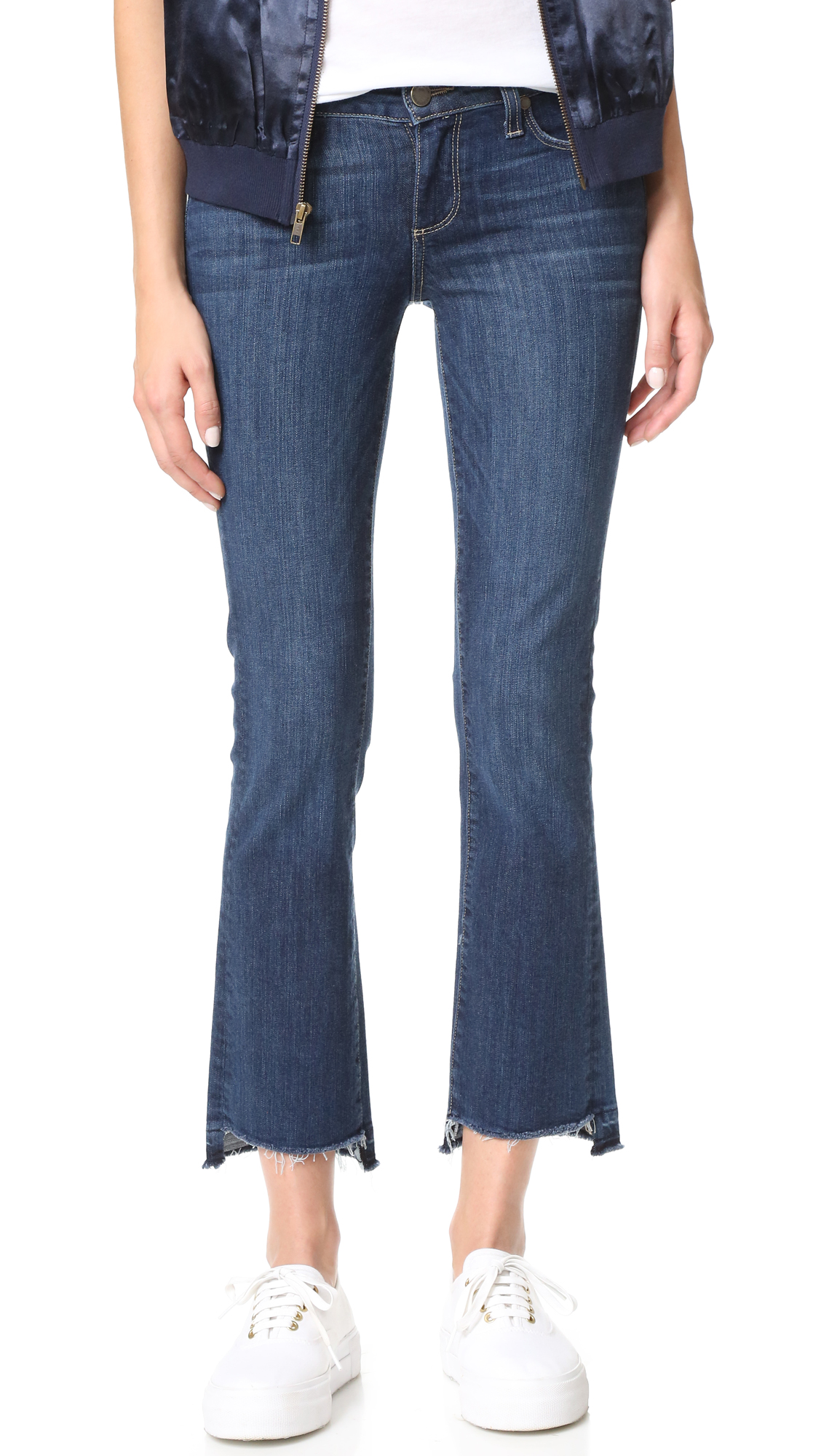 An undone, raw hem adds a worn feel to these cropped PAIGE flare jeans. 5 pocket styling. Button closure and zip fly. Fabric: Stretch denim. 91% cotton/7% polyester/2% elastane. Wash cold. Made in the USA. Measurements Rise: 8.25in / 21