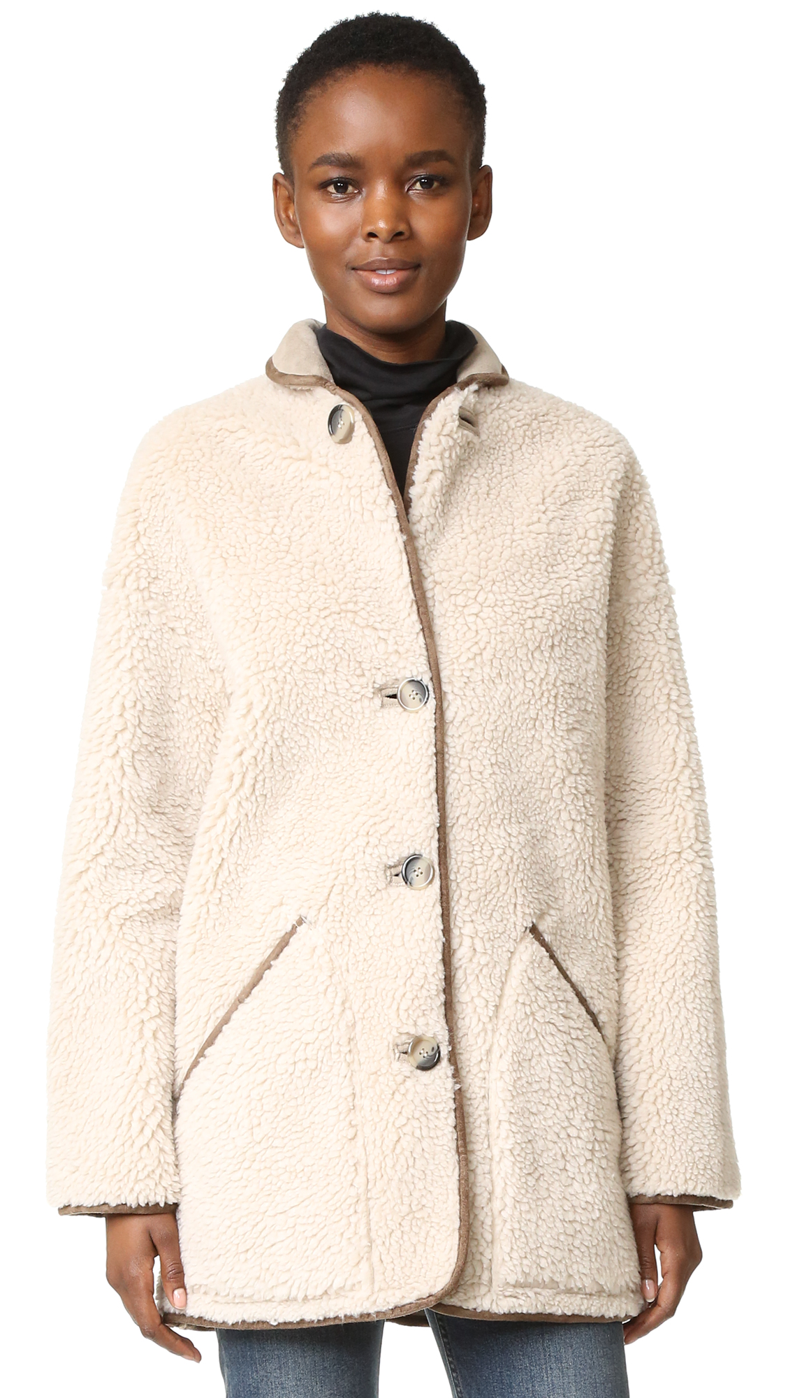 A reversible Paul Smith coat in luxe faux shearling and faux suede. Fold over collar and button placket. Slant hip pockets. Long sleeves. Fabric: Faux shearling / faux suede. 100% polyester. Dry clean. Imported, China. Measurements Length: 31.5in / 80
