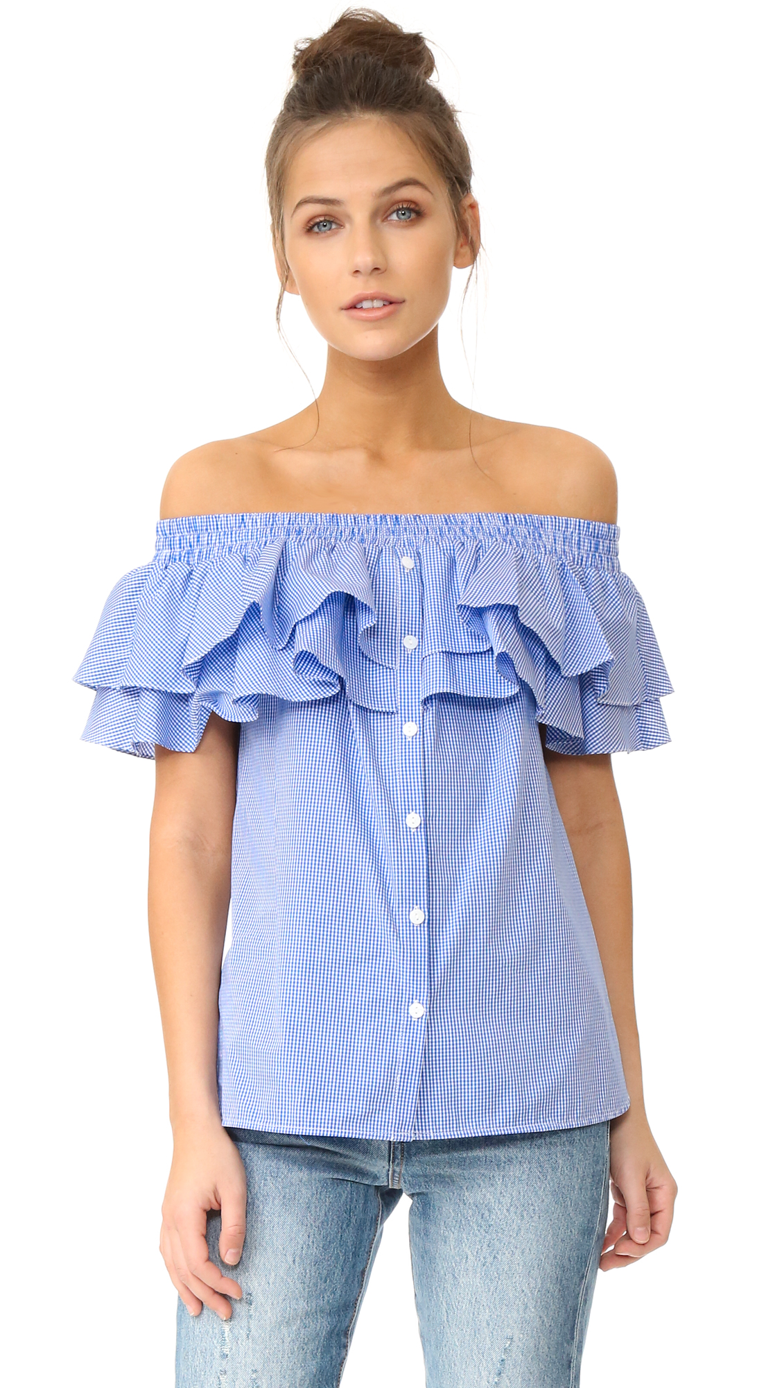 Tiered ruffles trim the off shoulder neckline on this gingham Petersyn blouse. Button front closure. Short sleeves. Fabric: Crisp weave. 100% cotton. Dry clean. Made in the USA. Measurements Length: 19.75in / 50cm, from center back Measurements from