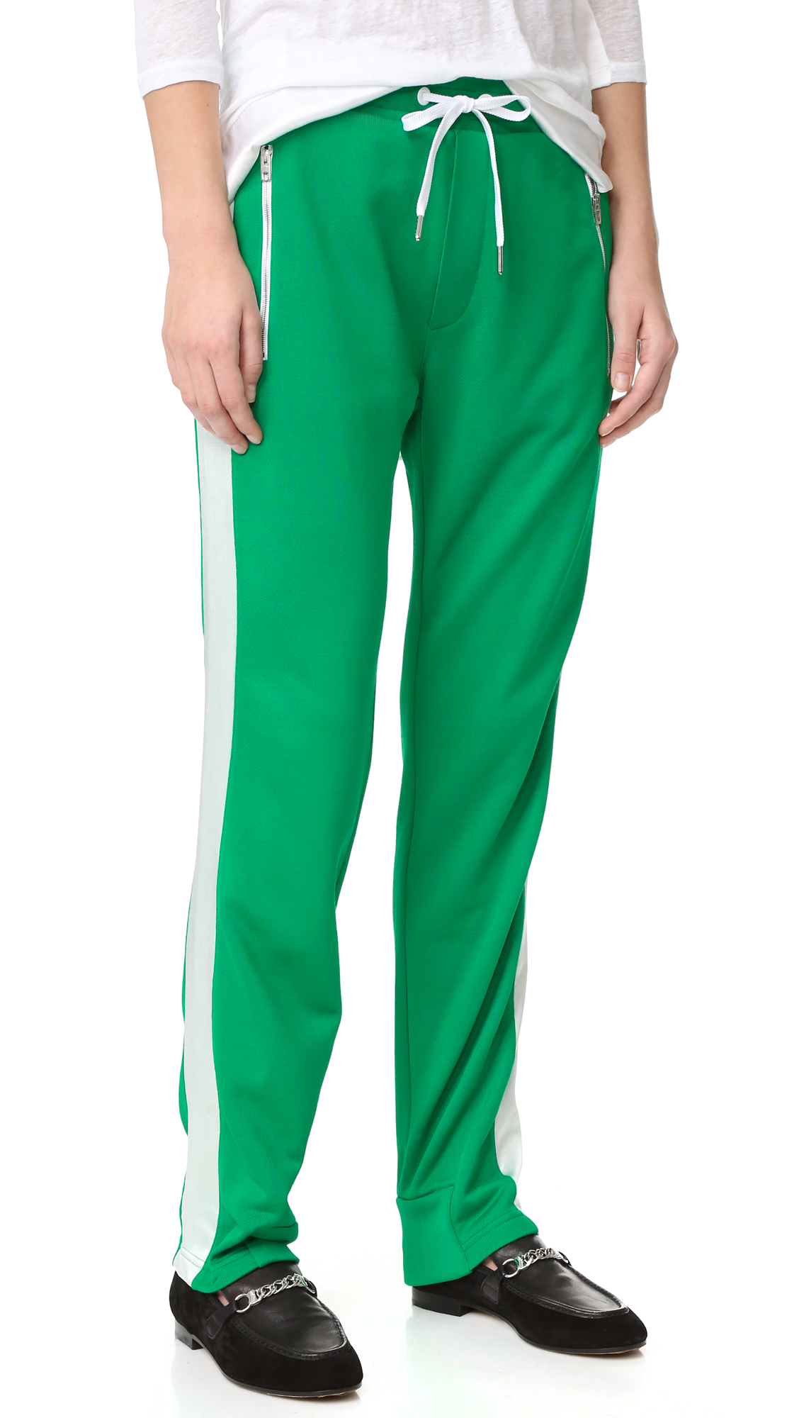 Sporty Rag & Bone track pants, styled with lustrous satin side stripes and zipper pockets. Covered elastic waistband with drawstring. Faux fly. Fabric: French terry. Shell: 59% polyester/41% cotton. Trim 1: 100% silk. Trim 2: 95% polyester/5% spandex. Wash cold. Made in
