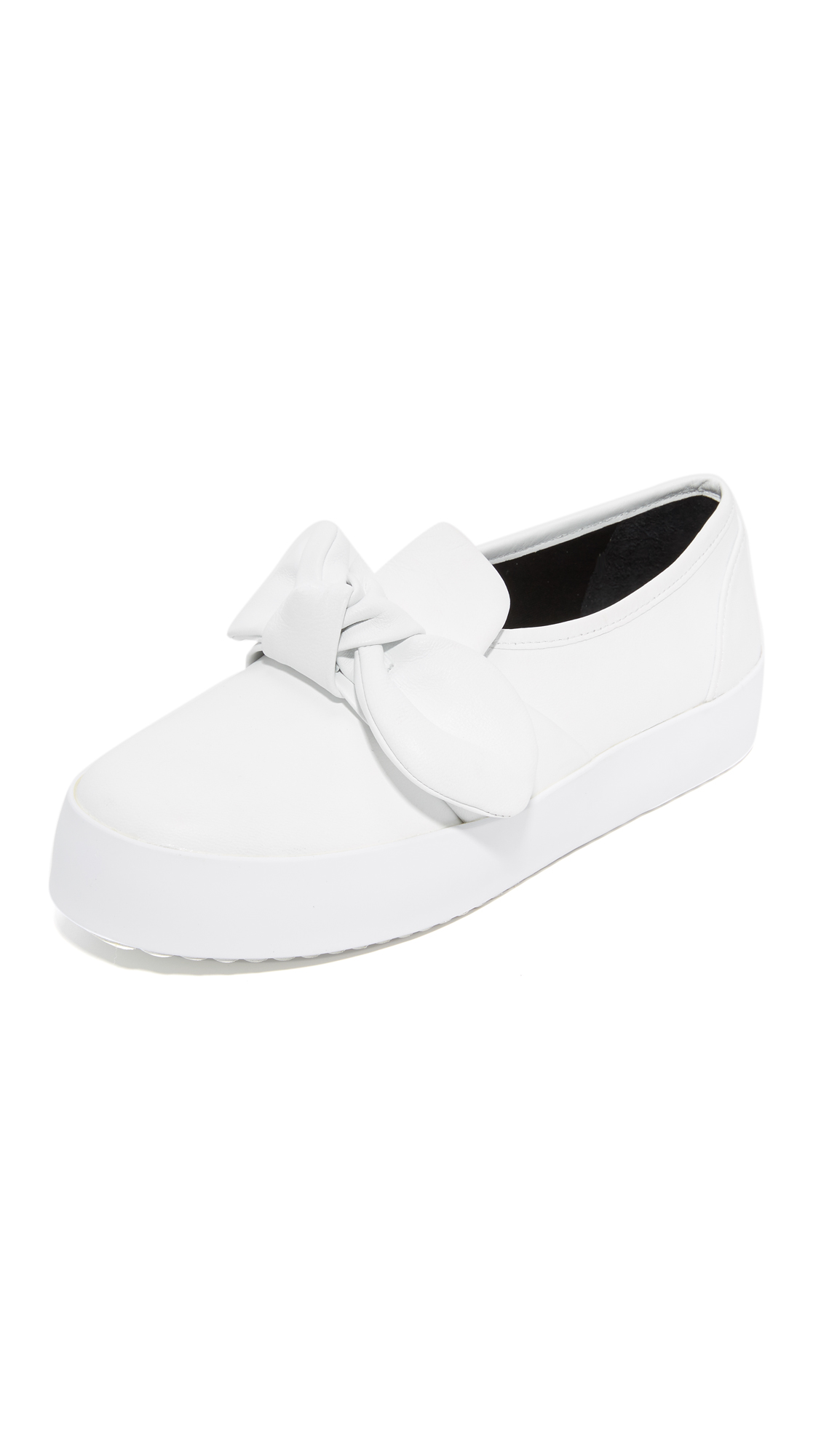 Sturdy leather Rebecca Minkoff slip on sneakers styled with a knotted bow at the vamp. Hidden elastic gore insets. Padded footbed and rubber sole. Leather: Cowhide. Imported, China. This item cannot be gift boxed. Measurements Platform: 1.25