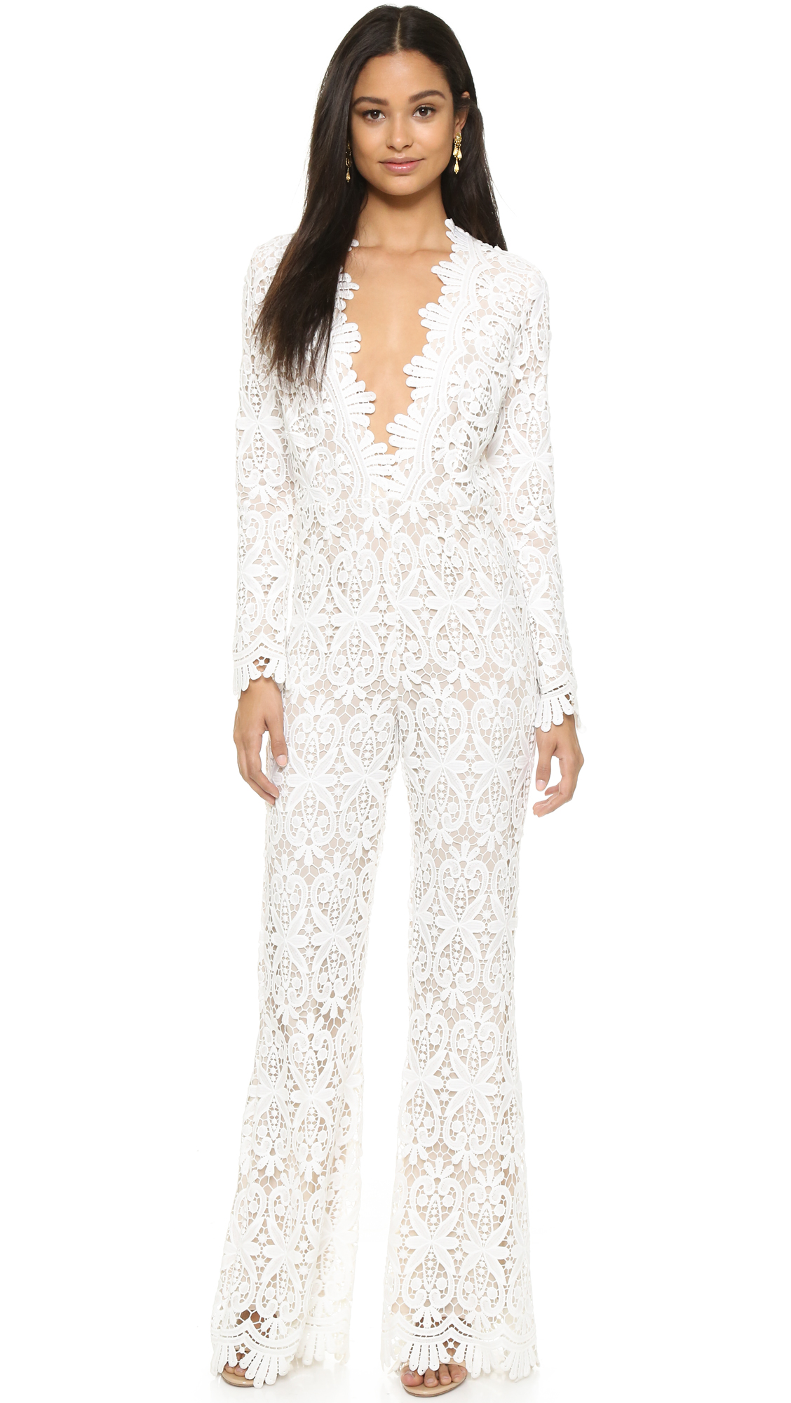 Texture rich lace composes this tailored Stone Cold Fox jumpsuit. Scalloped edges at the deep V neckline. Long sleeves. Flared leg styling. Hidden back zip. Lined. Fabric: Silk lace. 100% silk. Dry clean. Made in the USA.