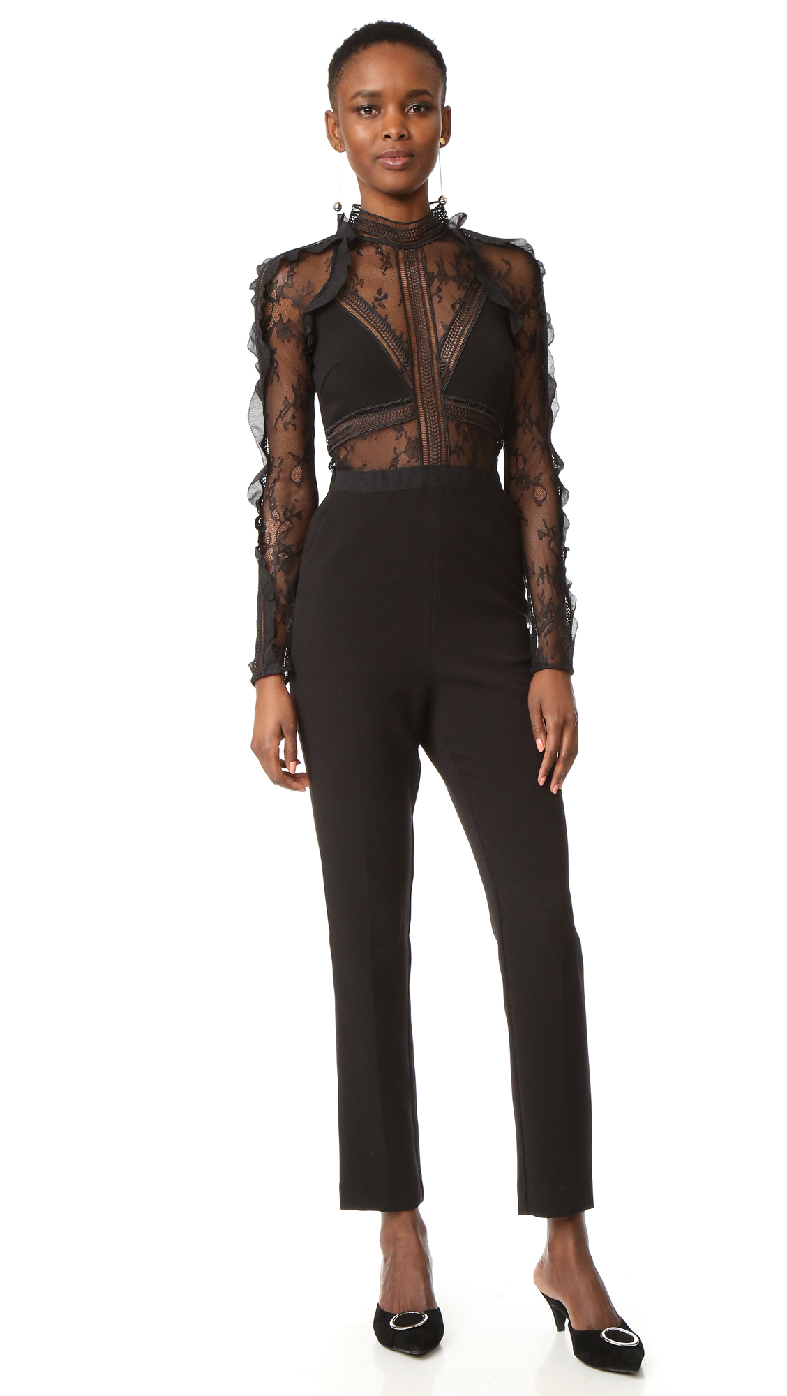 Sheer lace insets and picot edged ruffles add a hint of dark romance to this straight leg Self Portrait jumpsuit. Slant front pockets and welt back pocket. High neckline. Sheer long sleeves. Hidden back zip. Fabric: