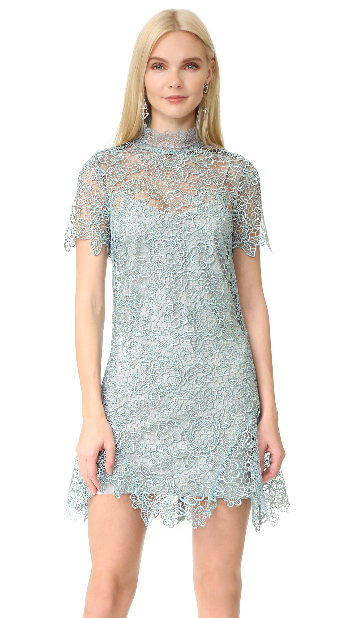 Delicate floral lace brings romantic, feminine style to this Self Portrait mini dress. Flared insets accent the hem, adding flirty swing. High neckline. Sheer sleeves. Exposed zip and grosgrain ribbon ties in back. Optional slip dress