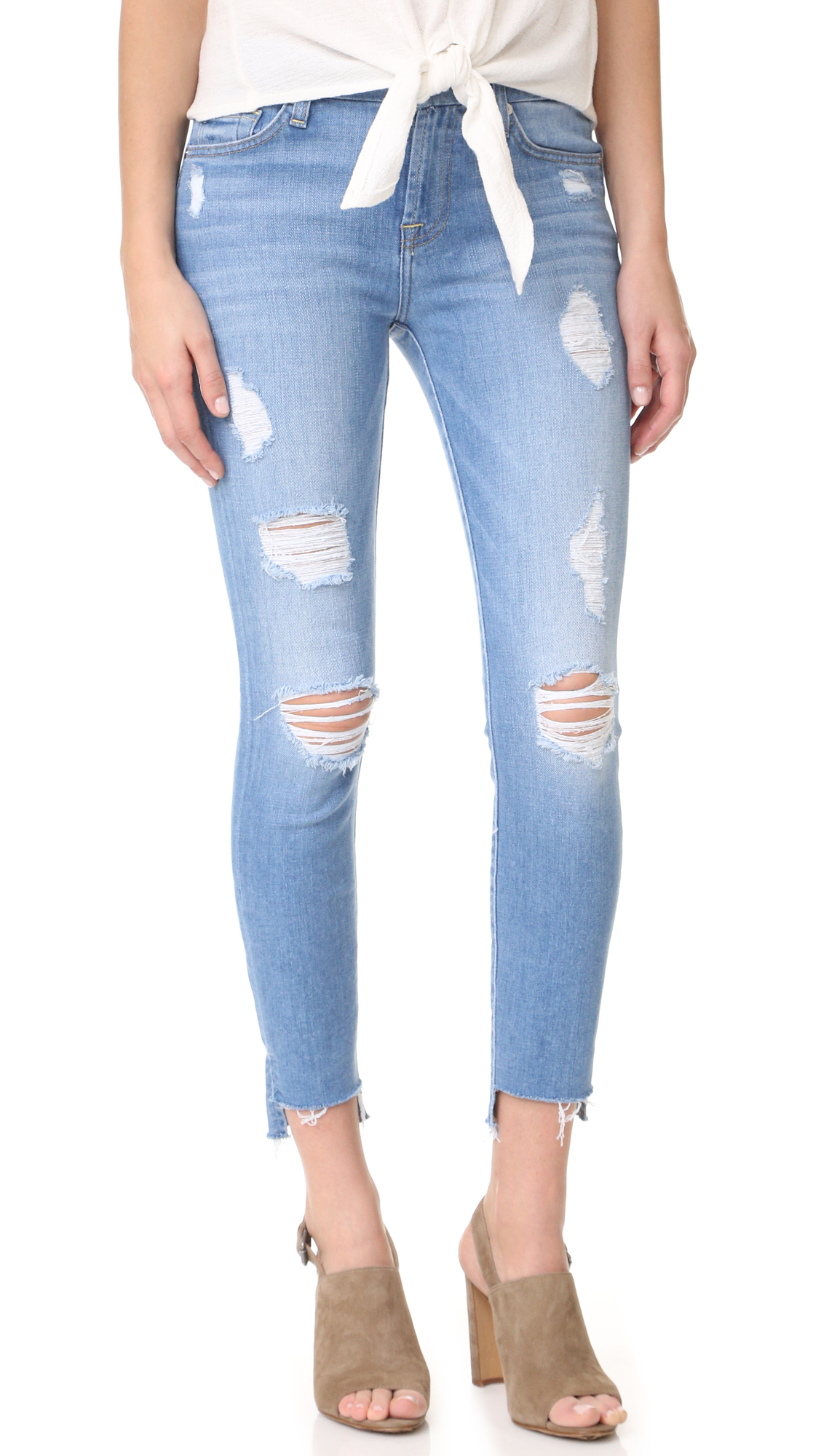 Shredded holes and frayed step hem cuffs bring a worn in feel to these faded 7 For All Mankind skinny jeans. 5 pocket styling. Button closure and zip fly. Fabric: Stretch denim. 94% cotton/5% polyester/1% spandex. Dry clean or