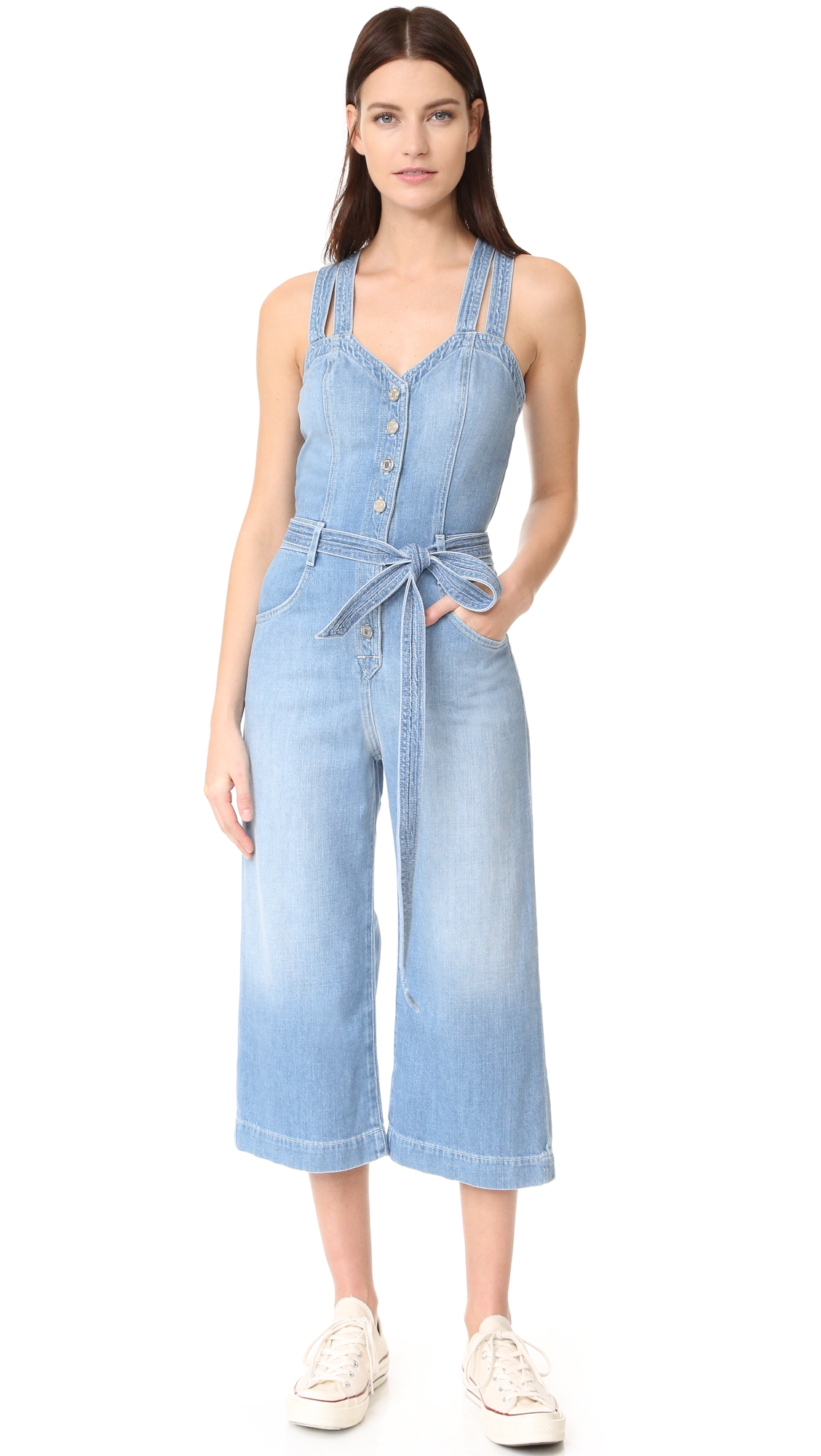 This cropped 7 For All Mankind jumpsuit is crafted in faded denim. Button half placket. Slant hip pockets and patch back pockets. Double crossover shoulder straps. Fabric: Denim. 82% cotton/18% rayon. Wash cold or dry clean. Imported, Mexico.