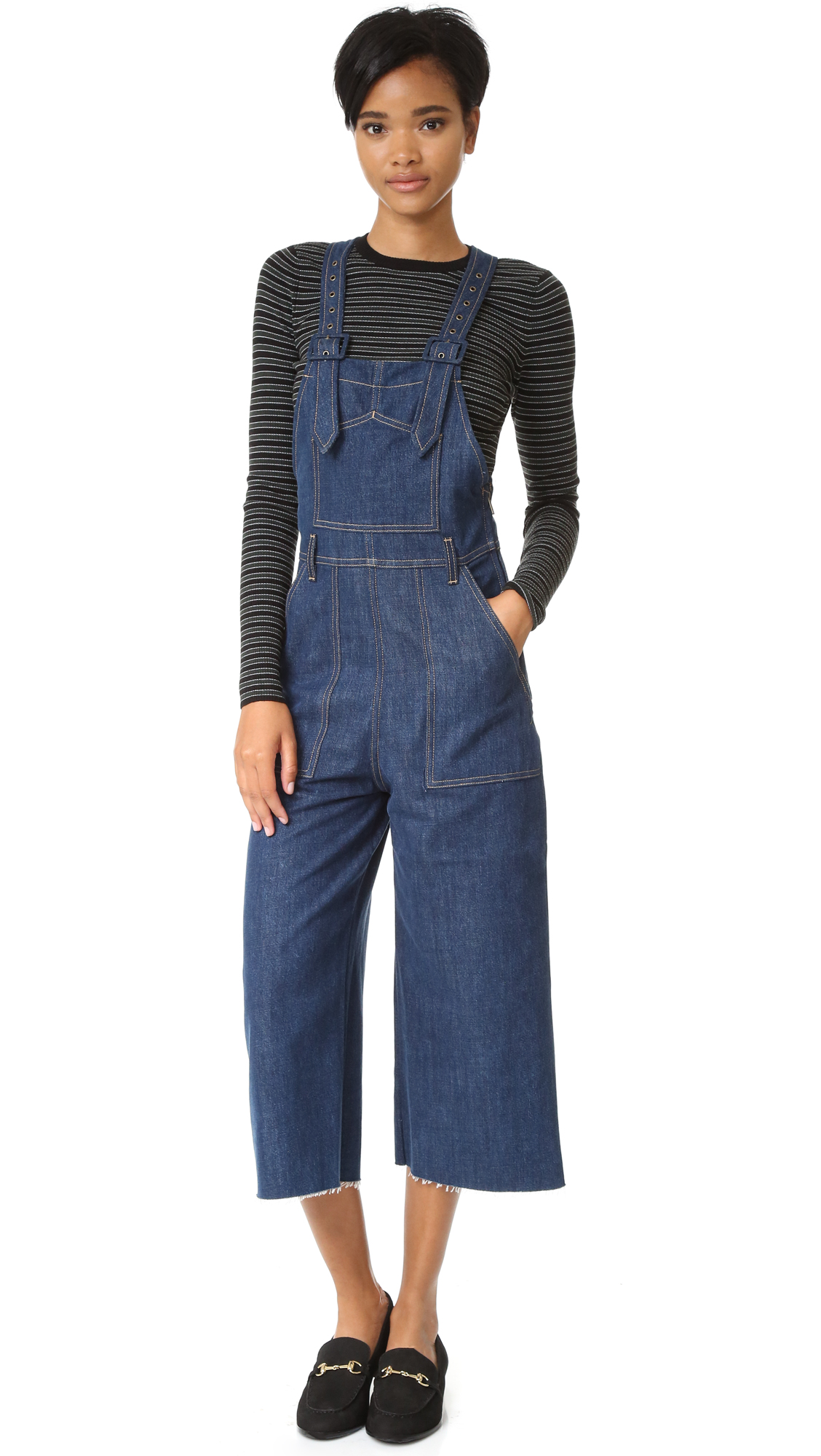 Charming Siwy overalls with a touch of retro style. Denim covered buckles fasten the adjustable straps. Classic 5 pocket styling. Raw cuffs. Hidden side zip. Fabric: Stretch denim. 60% cotton/40% lyocell. Wash warm or dry clean. Made in