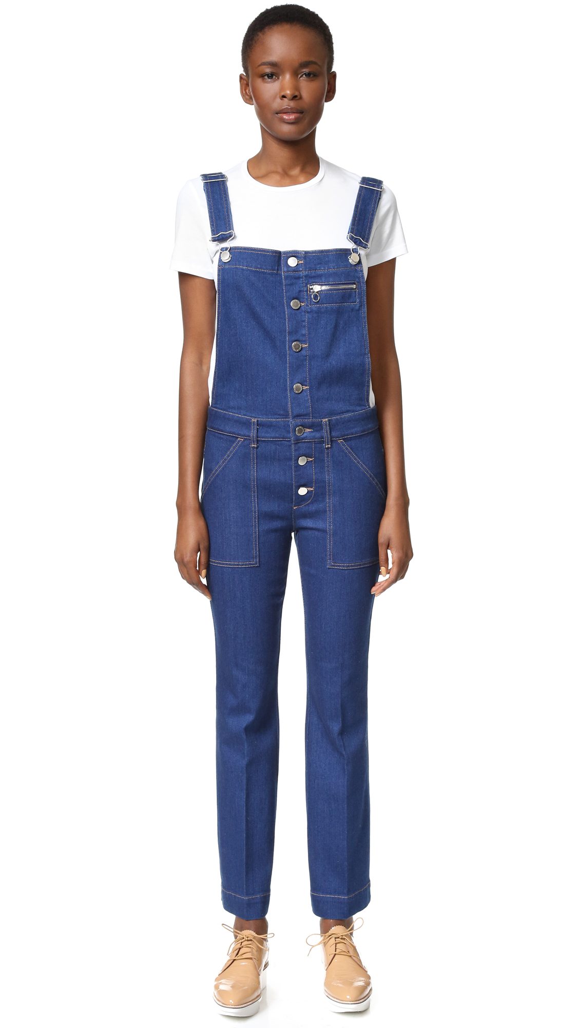 A wide leg Stella McCartney jumpsuit in classic denim. Logo buttons detail the placket and fasten the adjustable shoulder straps. Slant hip pockets and patch back pockets. Contrast top stitching. Fabric: Stretch denim. 92% cotton/6% elastomultiester/2% elastane.