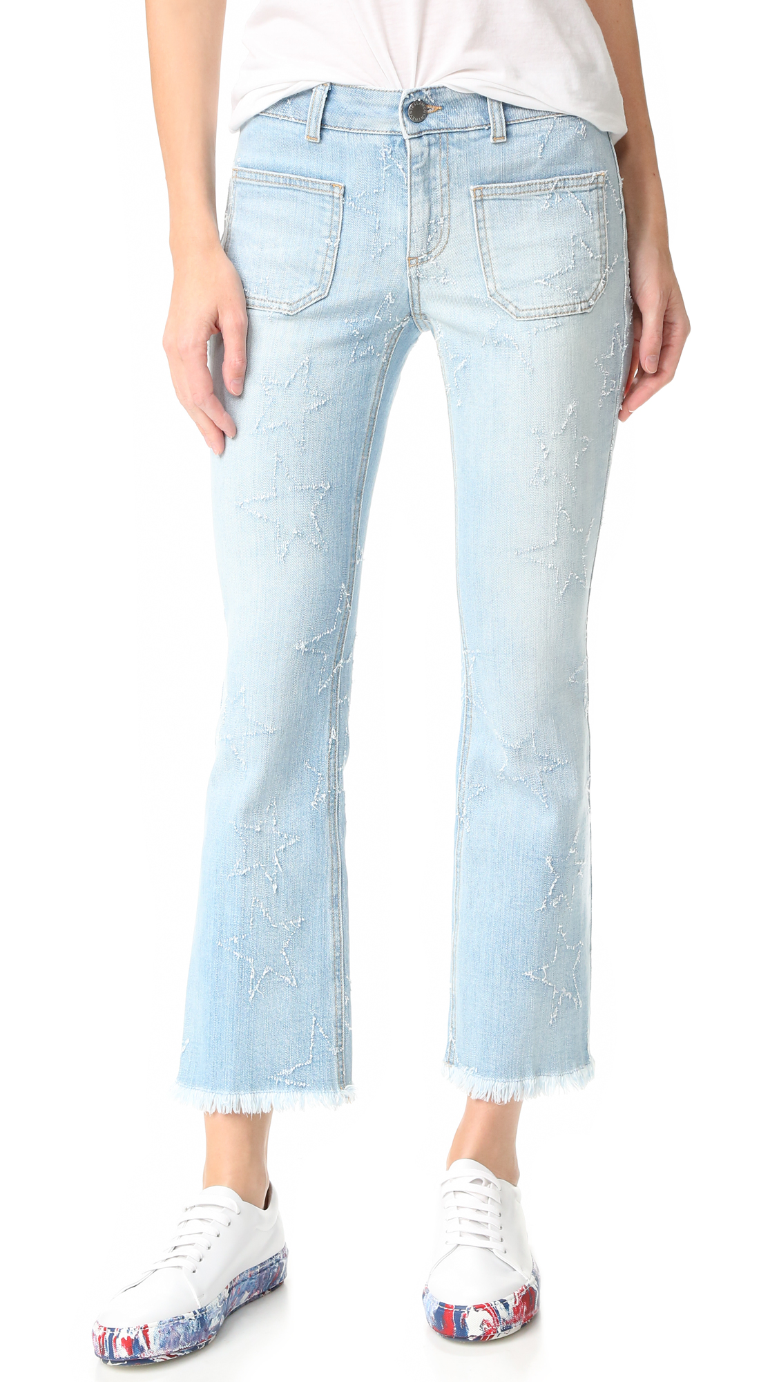 Runs small. Please see Size & Fit tab. Distressed stars accent these faded Stella McCartney jeans, and a frayed hem completes the undone look. 4 patch pockets. Button closure and zip fly. Fabric: Stretch denim. 98% cotton/2% elastane. Wash
