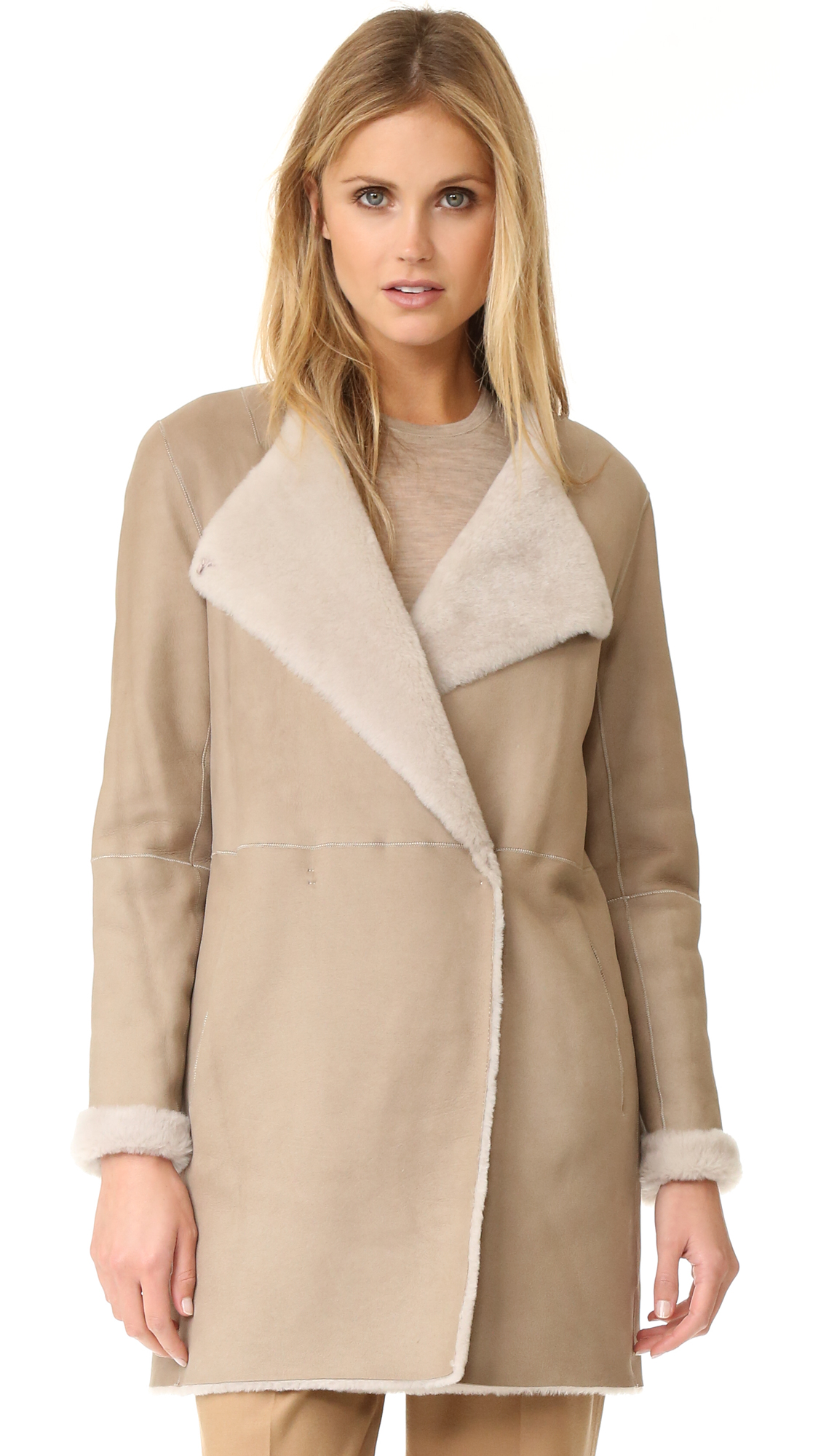 A reversible Theory coat made from cozy shearling. Hidden snaps fasten the off center placket. 2 pockets. Long sleeves. Unlined. Fur: Dyed lamb shearling, from Spain. Fur clean. Imported, Turkey. Measurements Length: 32.75in / 83cm, from shoulder Measurements