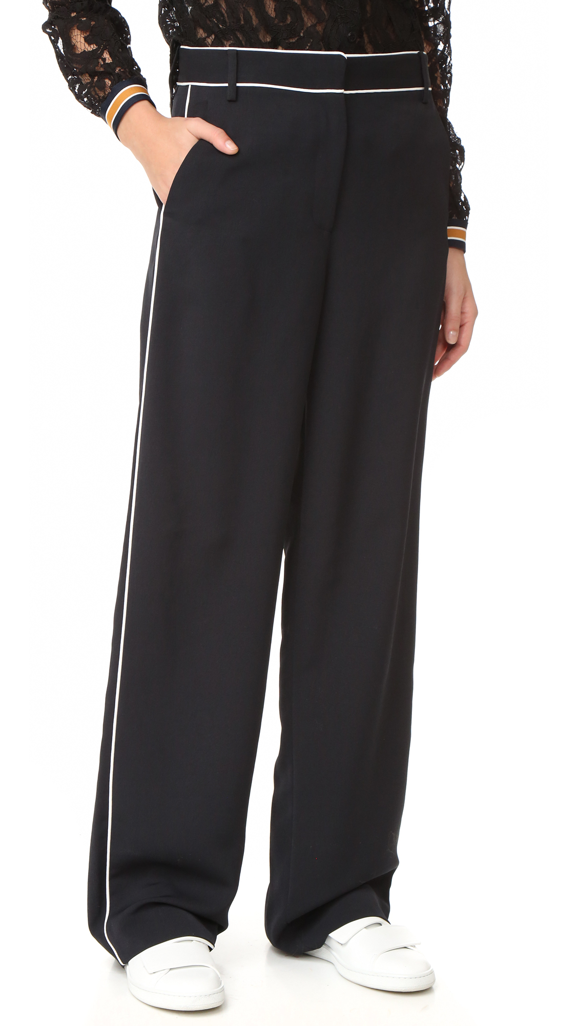 These luxe, pajama inspired Tibi trousers are finished with clean lined piping and oversized patch pockets. Slant hip pockets. Hook and eye closure and zip fly. Fabric: Luxe mid weight crepe. 100% polyester. Dry clean or wash