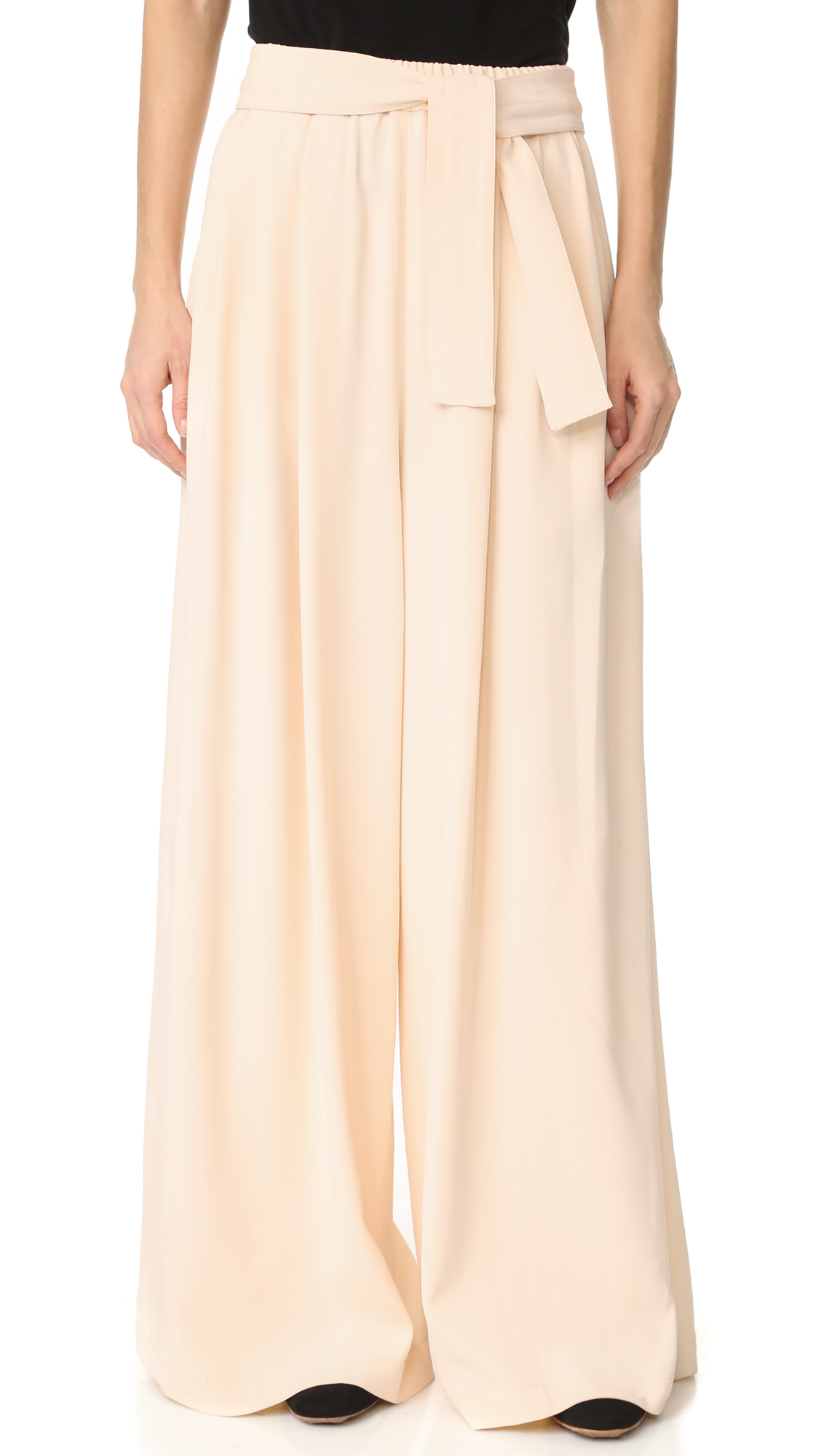 Pleated Tome wide leg pants with an effortless drape. Slant front pockets and patch back pockets. Smocked elastic waist. Optional, topstitched belt. Fabric: Crepe. 70% viscose/26% acetate/4% elastane. Dry clean. Made in the USA. Measurements Rise: 15.75in / 40