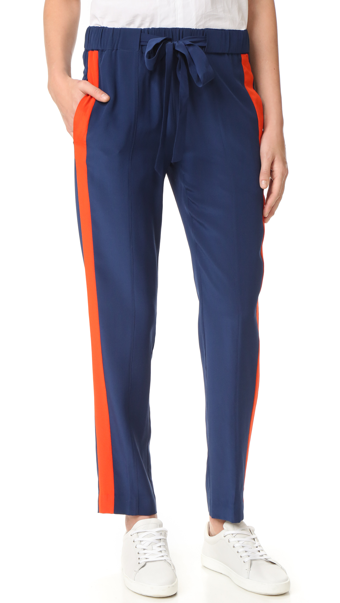 Bright tuxedo stripes add a bold pop of color to these relaxed silk Tory Burch track pants. Covered elastic waist with drawstring tie. On seam hip pockets. Fabric: Plain weave. 100% silk. Dry clean. Imported, China. Measurements