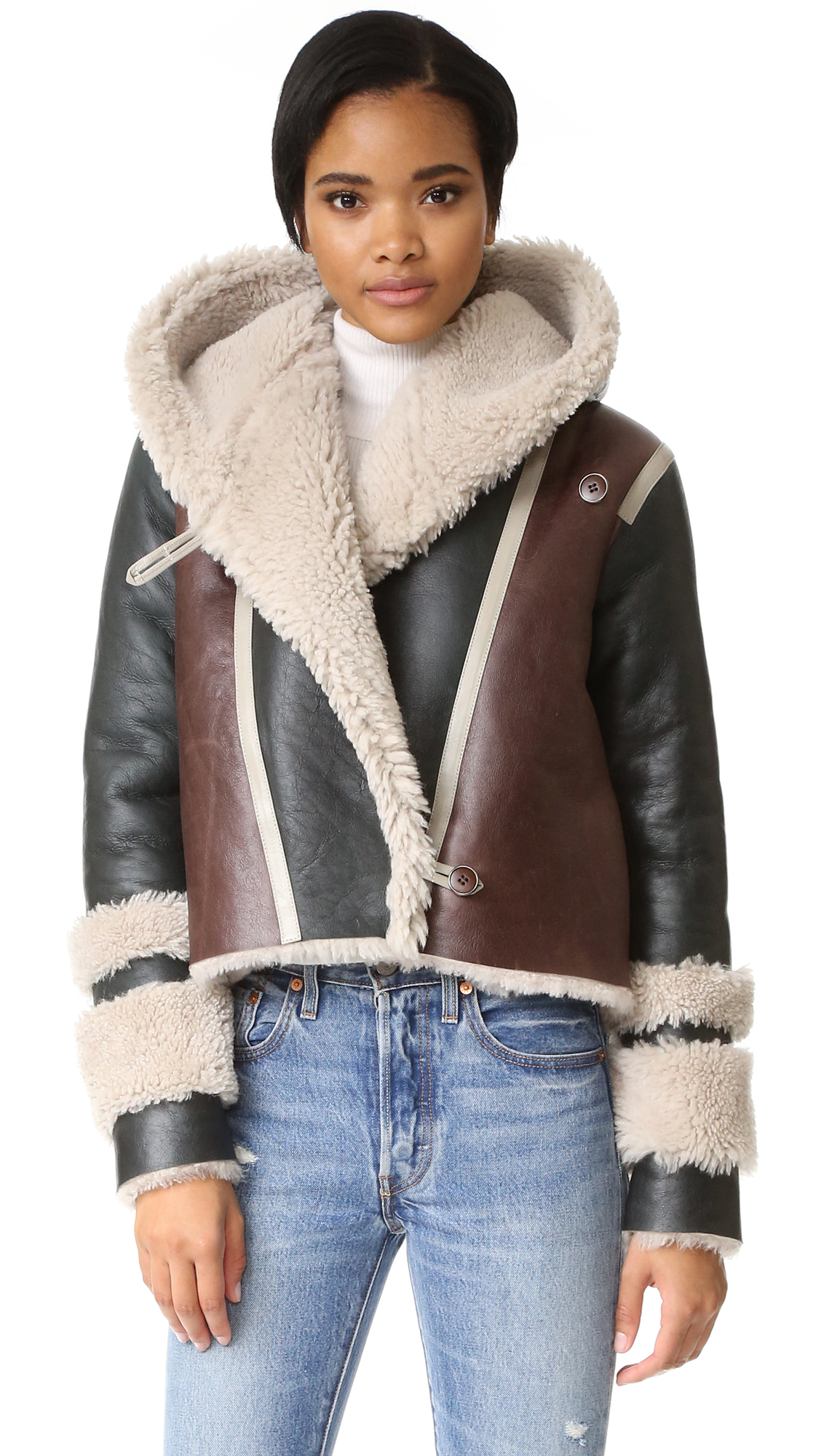 A hooded VEDA jacket made from plush, colorblock shearling. Button closures and on seam pockets. Long sleeves. Unlined. Fabric: Dyed lamb shearling, from Spain. Leather clean. Imported, Turkey. Measurements Length: 21.25in / 54cm, from shoulder Measurements from