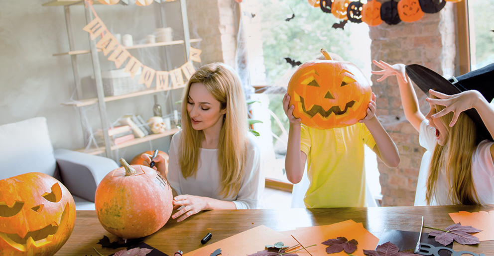 Woman carving pumpkin while children play with pumpkin and witches' hat.