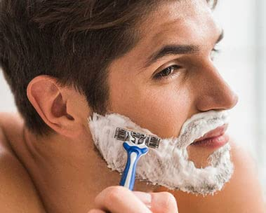 Man's face shaving with razor and shaving cream