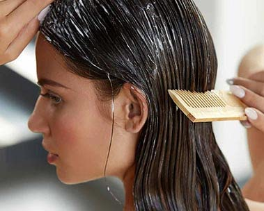Woman with long brown hair combing hair wet with soap
