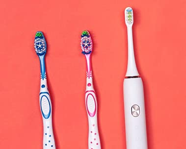 Two manual toothbrushes and one electric toothbrush on red background