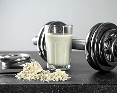 Nutritional shake in glass next to exercise weights