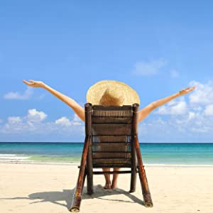 Woman sitting in chair on beach with arms in the air.