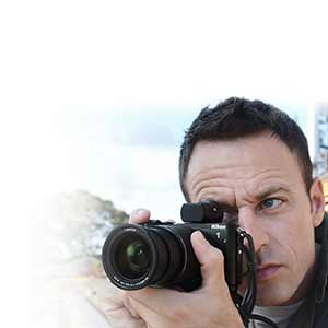 Man holding a Nikon 1 V3 to his eye as if shooting
