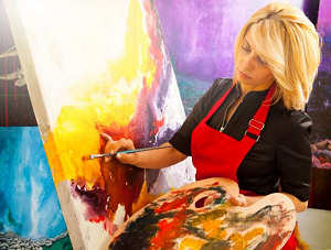 woman painting on an easel in bright light