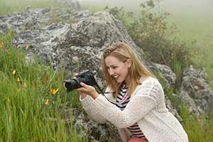 photo of woman with camera and AF-P DX NIKKOR 18-55mm f/3.5-5.6G VR lens