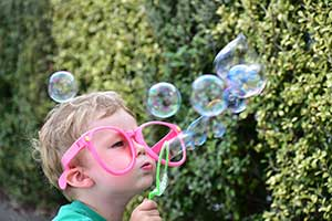 Photo of boy blowing bubbles, shot wwith AF-P DX NIKKOR 70-300mm f/4.5-6.3G ED lens highlighting zoom range