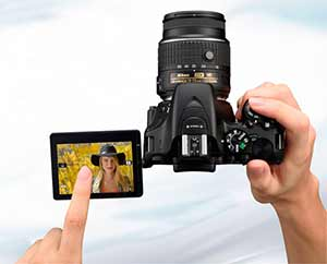 Photo of the D5500 DSLR with NIKKOR lens and image of a blonde woman on the LCD