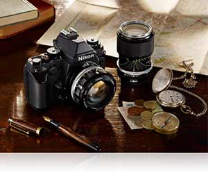 Photo of the Nikon Df and older NIKKOR lenses among items on a desk highlighting compatibility with legacy lenses