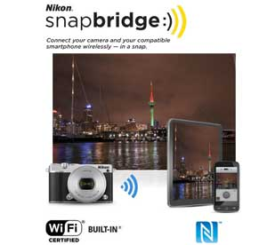 Nikon 1 J5 photo of a scene at night and the snapbridge logo and Wi-Fi graphics showing instant sharing