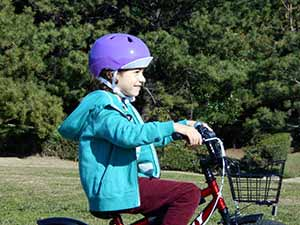 Nikon COOLPIX L32 photo of a girl riding a bike in a park, highlighting the zoom range of the camera