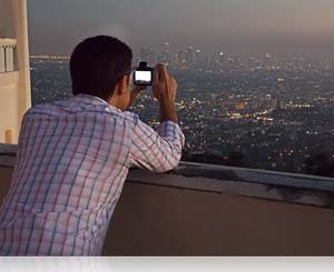 Photo of a man shooting a cityscape with the Nikon COOLPIX L620