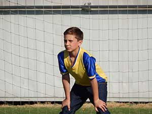 Nikon COOLPIX L830 photo of a boy in a soccer goal net showing Dynamic Fine Zoom